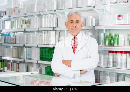 Pharmacist Standing Arms Crossed In Pharmacy - Stock Photo