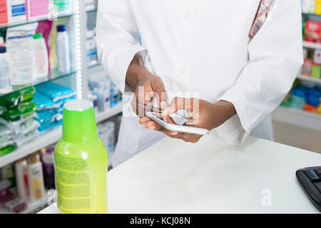 Female Pharmacist Using Smartphone Credit Card Reader At Counter - Stock Photo