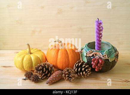 Seasonal Decorations with Vibrant Color Ripe Pumpkins, Many Pine Cones and Purple Candle in Grape Motif Holder - Stock Photo