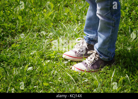 Boy in blue sneakers and jeans standing on the green grass sunny day in summer. Close up leg's shot. - Stock Photo
