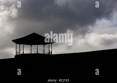 Silhouette of bandstand at top of hill against dark, moody clouds in sky - Stock Photo