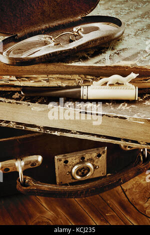 Leather suitcase with old books, ivory cigarette holder and pince-nez in a metal box on a wooden background. Retro - Stock Photo