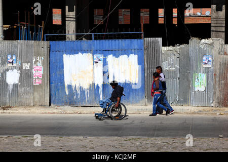 Disabled man in wheelchair on pavement in front of building site, El Alto, Bolivia - Stock Photo