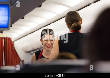 Munich, Germany - September 21th, 2017: Two female flight attendants are serving the meal in the economy class , - Stock Photo