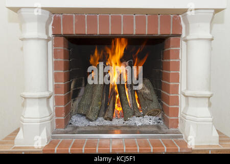 White fireplace with a burning fire - Stock Photo