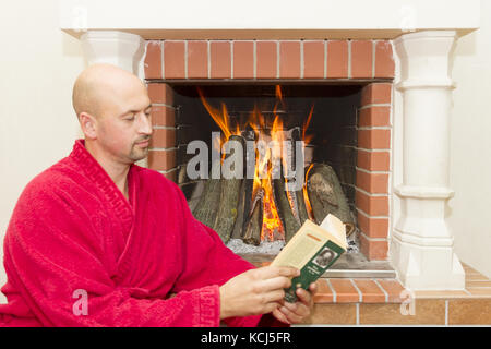 young man reading a book near the fireplace - Stock Photo