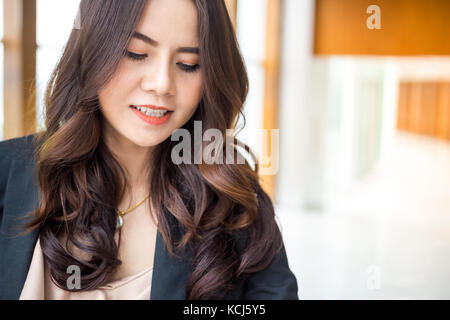 Beautiful Asia business woman over blue office background. - Stock Photo