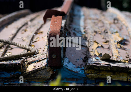 The rusty and decaying hull of a wooden boat, in need of attention - photo. - Stock Photo