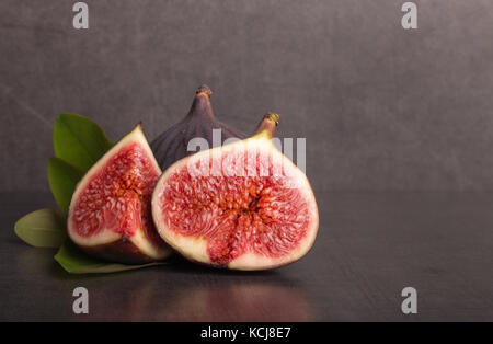 ripe fresh sliced figs on stone table - Stock Photo