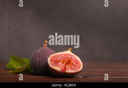 ripe fresh sliced figs on wooden table - Stock Photo