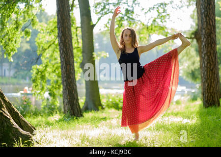 Caucasian woman in red skirt doing balance yoga asana in summer park. - Stock Photo