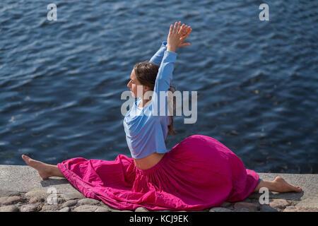 Sporty fit caucasian woman doing asana hanumanasana pose posture in nature. - Stock Photo