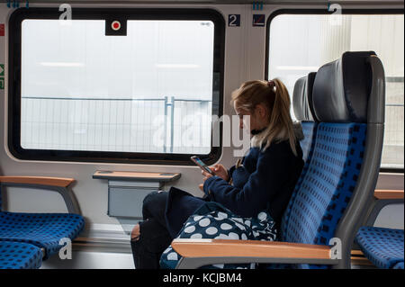 Pensive woman looking at her smartphone in a train - Stock Photo