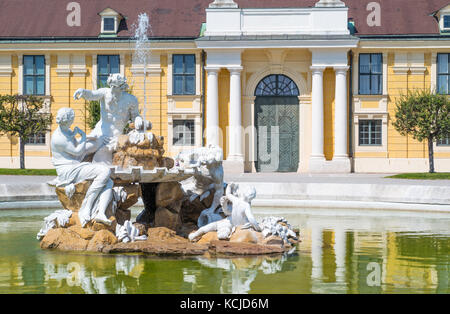 Vienna, Austria - August 7, 2016:  A fountain in front of the rear facade of the Schonbrunn Palace - Stock Photo
