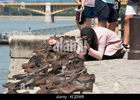 The Shoes on the Danube Bank memorial in Budapest on a sunny day with a tourist taking pictures. - Stock Photo