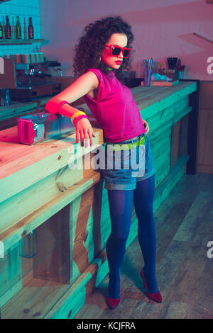 fashionable woman leaning on counter - Stock Photo