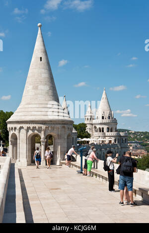 Tourists on the walls of the Fisherman's Bastion in Budapest looking at the view and taking photographs pictures - Stock Photo