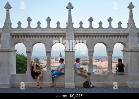 Four 4 people, two 2 couples tourists on the walls of the Fisherman's Bastion admiring the view of Budapest with - Stock Photo