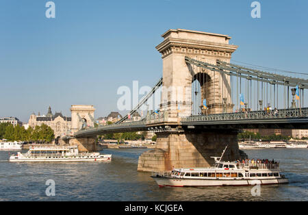 A view of the Széchenyi Chain Bridge in Budapest with a day trip river cruise boat passing underneath on a sunny - Stock Photo