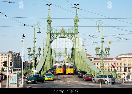 The Ganz CSMG tram in Budapest crossing the Liberty Bridge on a sunny day with blue sky. - Stock Photo