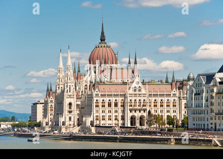 A view of the Hungarian Parliment Building on the Danube river in Budapest on a sunny day with blue sky. - Stock Photo