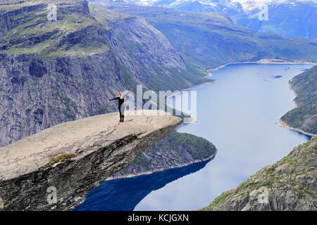 Woman Hiker posing and enjoying view from Trolltunga rock formation in Norway - Stock Photo