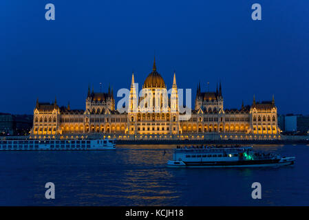 An evening nighttime view of the Hungarian Parliment Building on the Danube river in Budapest with a tourist river - Stock Photo