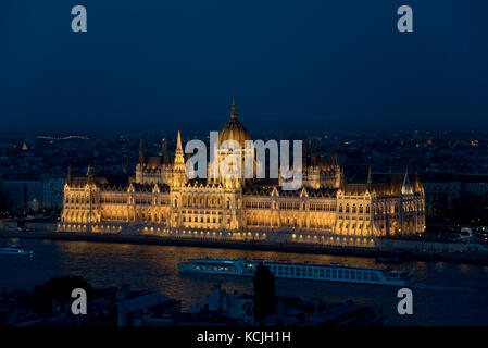 An aerial cityscape evening nighttime view of the Hungarian Parliment Building in Budapest with a tourist river - Stock Photo