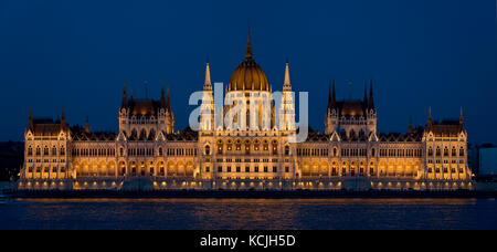 A 2 picture stitch evening nighttime view of the Hungarian Parliament Building on the Danube river in Budapest. - Stock Photo