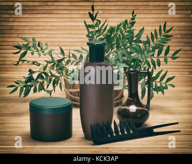 Natural hair care cosmetics. Shampoo, hair mask and comb with fresh green plant branches. Toned image - Stock Photo