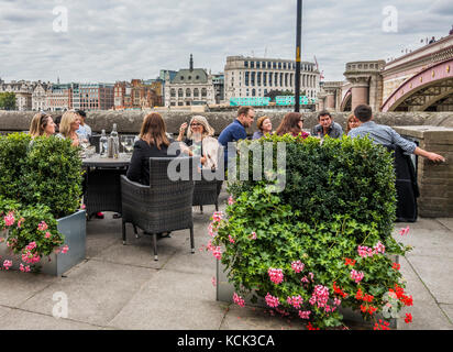 A group of people sitting having drinks outside Doggett's pub, right next to Victorian era Blackfriars Bridge, South - Stock Photo
