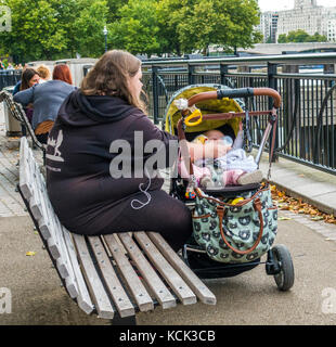 Overweight, single parent, teenage mother, sitting on a wooden bench, bottle feeding milk to her baby in a pushchair, - Stock Photo