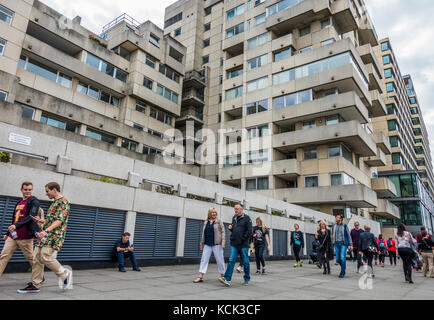 People walking past old concrete apartment blocks, facing the River Thames on Bankside, London, England, UK. - Stock Photo