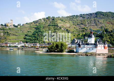 The town of Kaub on the river Rhine in Germany with castle Pfalz in the foreground - Stock Photo