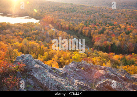 Autumn trees in full color with rocky cliff edge at Lake of the Clouds Michigan. Taken at sunrise. - Stock Photo
