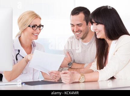 Happy Doctor Discussing With Couple In Clinic - Stock Photo
