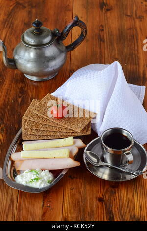 Metal plate with crispbread, cheese, cottage cheese, ham, cherry tomato, cup of coffee, coffee pot on a wooden background. - Stock Photo