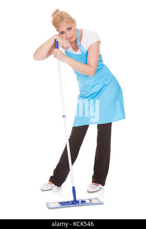 Tired Woman Leaning On Broom Over White Background - Stock Photo