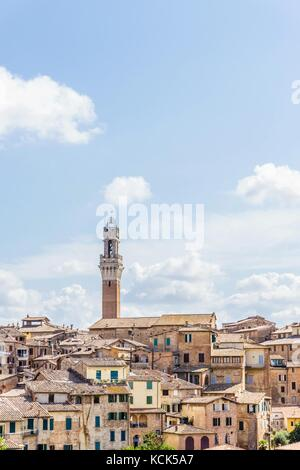 Vertical photo with view on the town hall tower in over the houses and buildings in historic ancient town Siena - Stock Photo