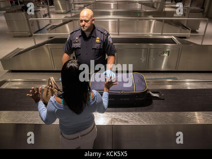 U.S. Customs and Border Protection Field Operations officers check luggage as they process international passenger - Stock Photo