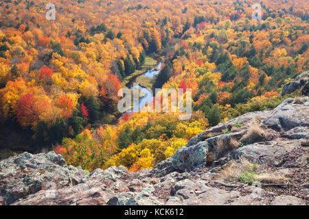 Trees in full autumn color and a small river viewed from rocky overlook in the Porcupine Mountains of Michigan - Stock Photo