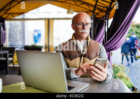 Old senior businessman in suit and tie with laptop computer and smartphone, sitting in city cafe house - Stock Photo