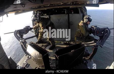 U.S. sailors conduct a live-fire exercise from a U.S. Navy MH-60S Seahawk helicopter over the ocean February 21, - Stock Photo
