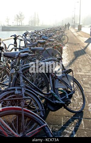 Snow covered bicycles parked in Amsterdam Centrum - Stock Photo