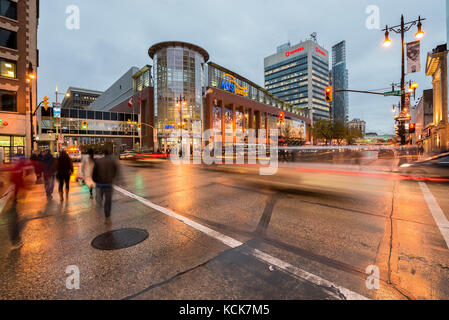 People crossing Portage Avenue in front of MTS Centre at dusk downtown Winnipeg in Manitoba, Canada - Stock Photo