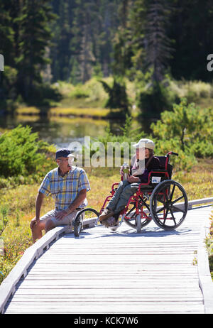 A physically handicapped woman and her paretner relax on a  boardwalk while enjoying an outing in Paradise Meadows - Stock Photo