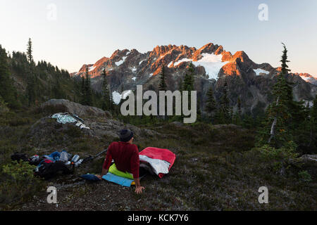 A lone hiker wakes up to early morning light scupting across the Septimus/Rousseau massif while hiking on the Flower - Stock Photo
