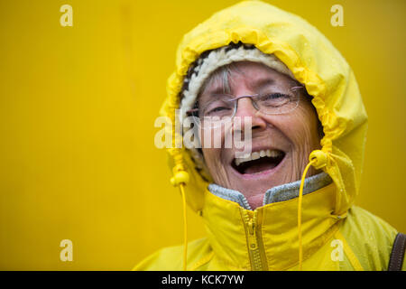 A happy, laughing senior citizen dressed up in her yellow rain slicker enjoys the stormy weather while aboard the - Stock Photo