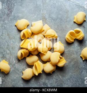 Conchiglie pasta on a gray stone background - Stock Photo