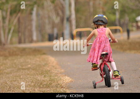 A child rides on a path - Stock Photo